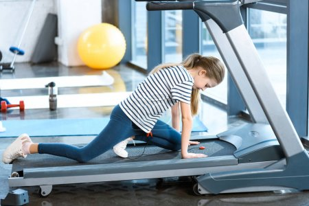 Girl stretching on treadmill before training
