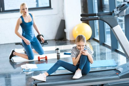 girl injured knee sitting on treadmill