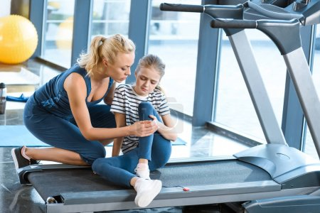 Woman helping girl injured knee sitting on treadmill