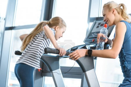 Woman trainer looking at small girl workout on treadmill