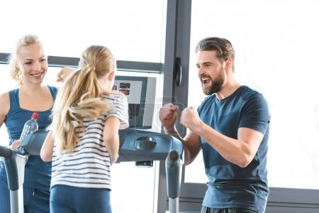 Parents supporting daughter workout on treadmill