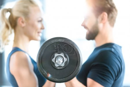 Loving couple exercising together with barbell at gym