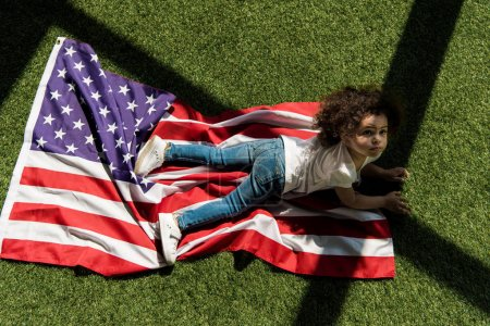 girl with american flag on grass