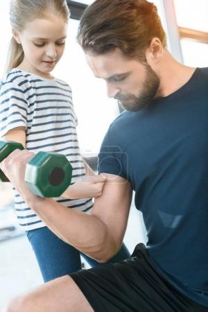 Photo for Girl looking at guy workout with dumbbell - Royalty Free Image