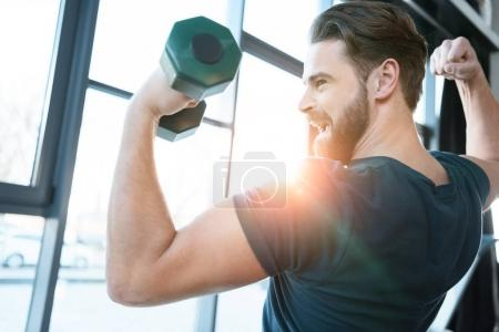 Photo for Handsome young guy workout with dumbbell - Royalty Free Image
