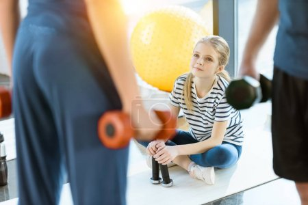 Fitness people exercising with dumbbells while teenage girl sitting on mat at fitness studio