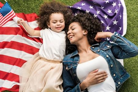 Photo for Young african american woman resting with daughter on grass with american flag - Royalty Free Image