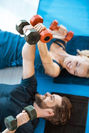 Couple of young fitness people exercising with dumbbells at fitness studio