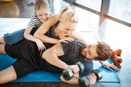 Happy family having fun at gym, man holding dumbbells