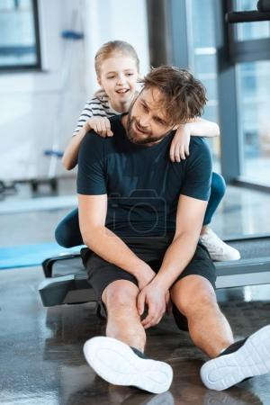 girl embrace tired father sitting after workout on treadmill at gym