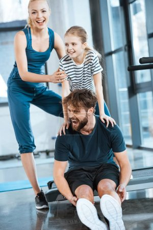 Woman with girl embrace tired father sitting on treadmill at gym