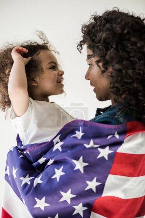 Photo pour La chère mère afro-américaine recouverts de drapeau américain embrasser fille - image libre de droit