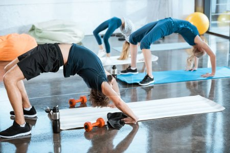 People doing gymnastics, performing Bridge pose at fitness studio