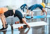 People doing gymnastics, performing Bridge pose at fitness studio