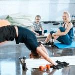 People doing gymnastics, man performing bridge pose at fitness studio