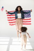 Woman and daughter jumping with american flag
