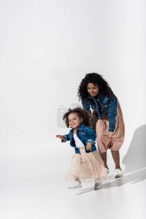 Photo for Lovely african american family, mother and daughter having fun on white background - Royalty Free Image