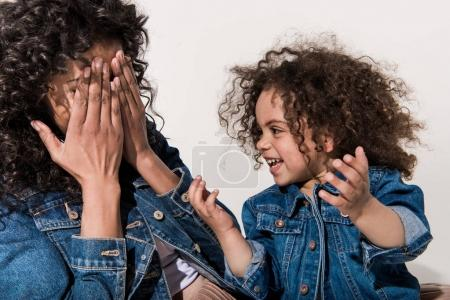 mother playing hide-and-seek with daughter
