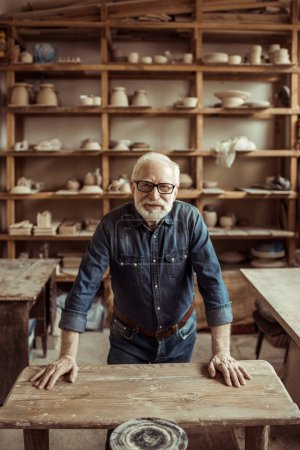 Front view of senior potter standing and leaning on table against shelves with pottery goods at workshop