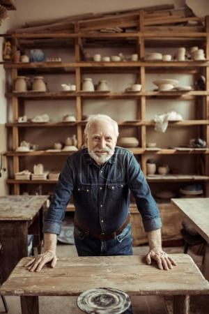 Photo for Front view of senior potter standing and leaning on table against shelves with pottery goods at workshop - Royalty Free Image