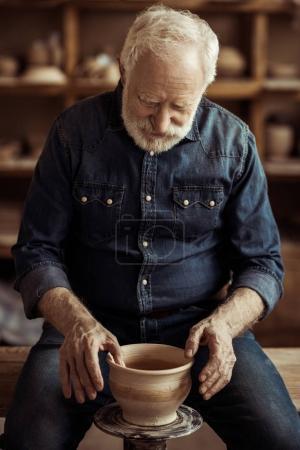 Senior potter making pottery on a wheel at workshop