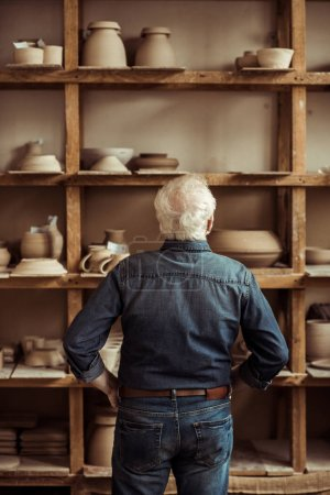 Rear view of senior potter standing near shelves with pottery goods and searching something at workshop