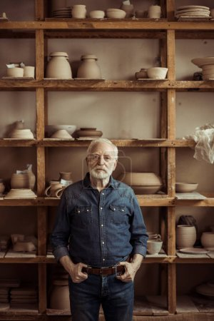 Front view of senior potter standing against shelves with pottery goods at workshop