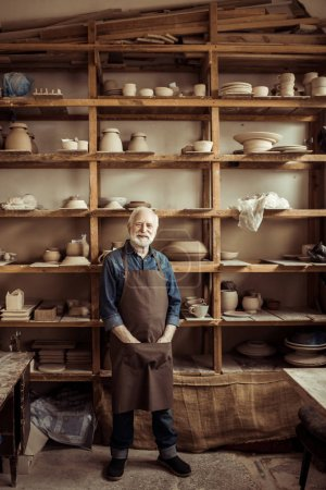 Front view of senior potter in apron standing against shelves with pottery goods at workshop