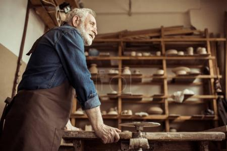Side view of senior potter in apron standing and leaning on table against shelves with pottery goods at workshop