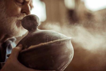 Close up of senior potter in apron examining ceramic bowl at workshop