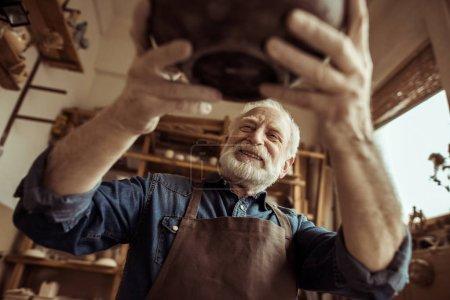 Photo pour Potier senior dans un tablier examinant un bol en céramique à l'atelier - image libre de droit