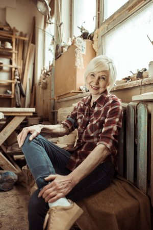 Happy senior woman sitting on bench near window at workshop