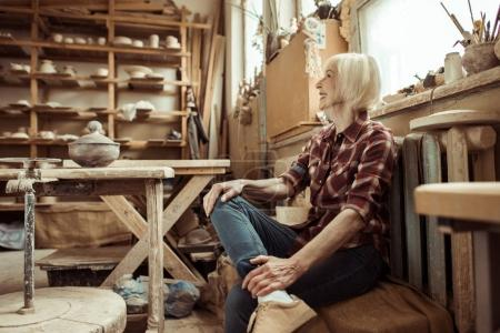 Photo for Happy senior woman sitting on bench near window at workshop - Royalty Free Image