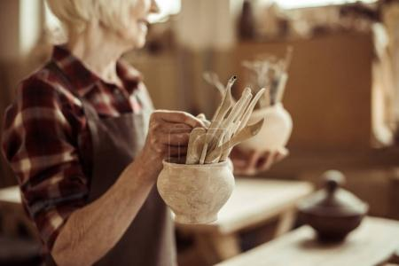 Senior woman holding bowls with pottery tools at at workshop