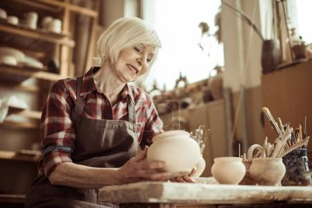 Female potter sitting at table and examining ceramic bowl at workshop