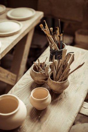 Photo pour Gros plan des pinceaux avec des outils de poterie dans des bols sur la table - image libre de droit