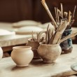 Close up of paint brushes with pottery tools in bo...