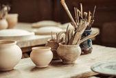 """Постер, картина, фотообои """"Закройте кисти с керамическими инструментами в чашках на столе"""""""