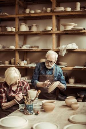 Photo for Woman painting clay pot with senior potter at workshop - Royalty Free Image