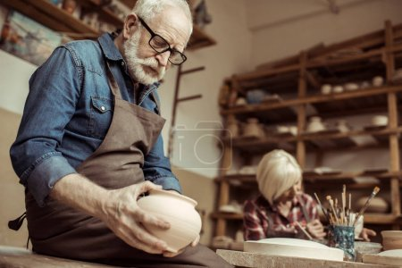 Senior potter in apron and eyeglasses examining ceramic bowl with woman working on background