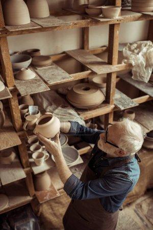 Foto de Potter Senior en delantal y anteojos examen tazón de cerámica en el taller - Imagen libre de derechos