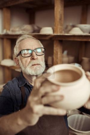 Senior potter in apron and eyeglasses examining ceramic bowl at workshop