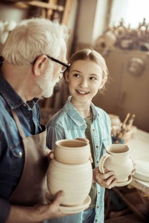 Granddaughter and grandfather holding and examining clay goods