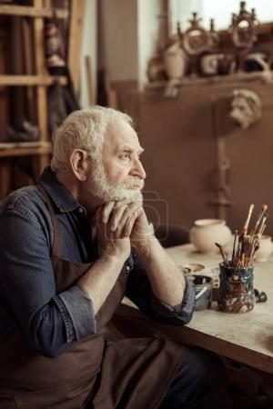 Photo for Senior potter in apron sitting at table and daydreaming at manufacturing - Royalty Free Image