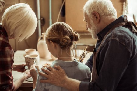 Rear view of girl painting clay pot and grandparents helping at workshop