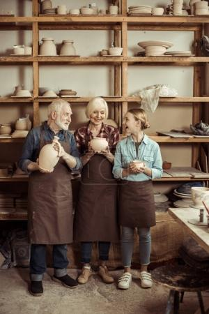 Granddaughter and grandparents standing and holding clay vase and bowls against wall with pottery goods