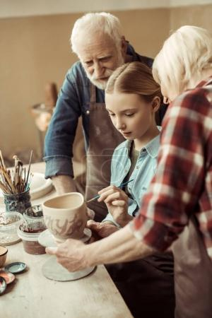 Photo pour Vue de côté du pot en argile peinture fille et les grands-parents, aidant à l'atelier - image libre de droit