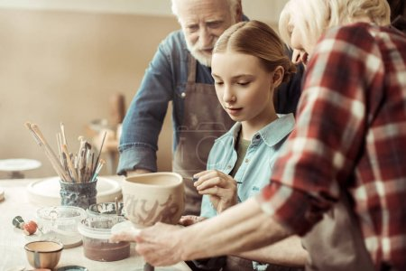 Side view of girl painting clay pot and grandparents helping at workshop