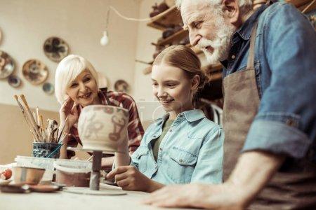 Photo pour Vue de face du pot en argile peinture fille et les grands-parents, aidant à l'atelier - image libre de droit
