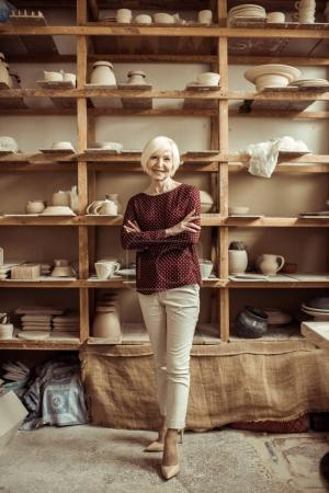 Front view of senior female potter standing at workshop